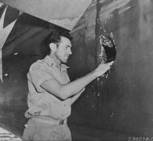 "1st Lt Louis Zamperini, peers through a hole in his B-24D Liberator Super Man made by a 20mm shell over Nauru, April 18, 1943"" From The National Archives via Wikimedia Commons."